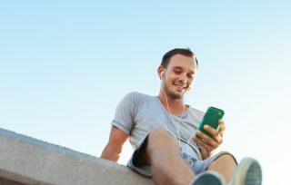 vyras naudojasi mobiliuoju telefonu